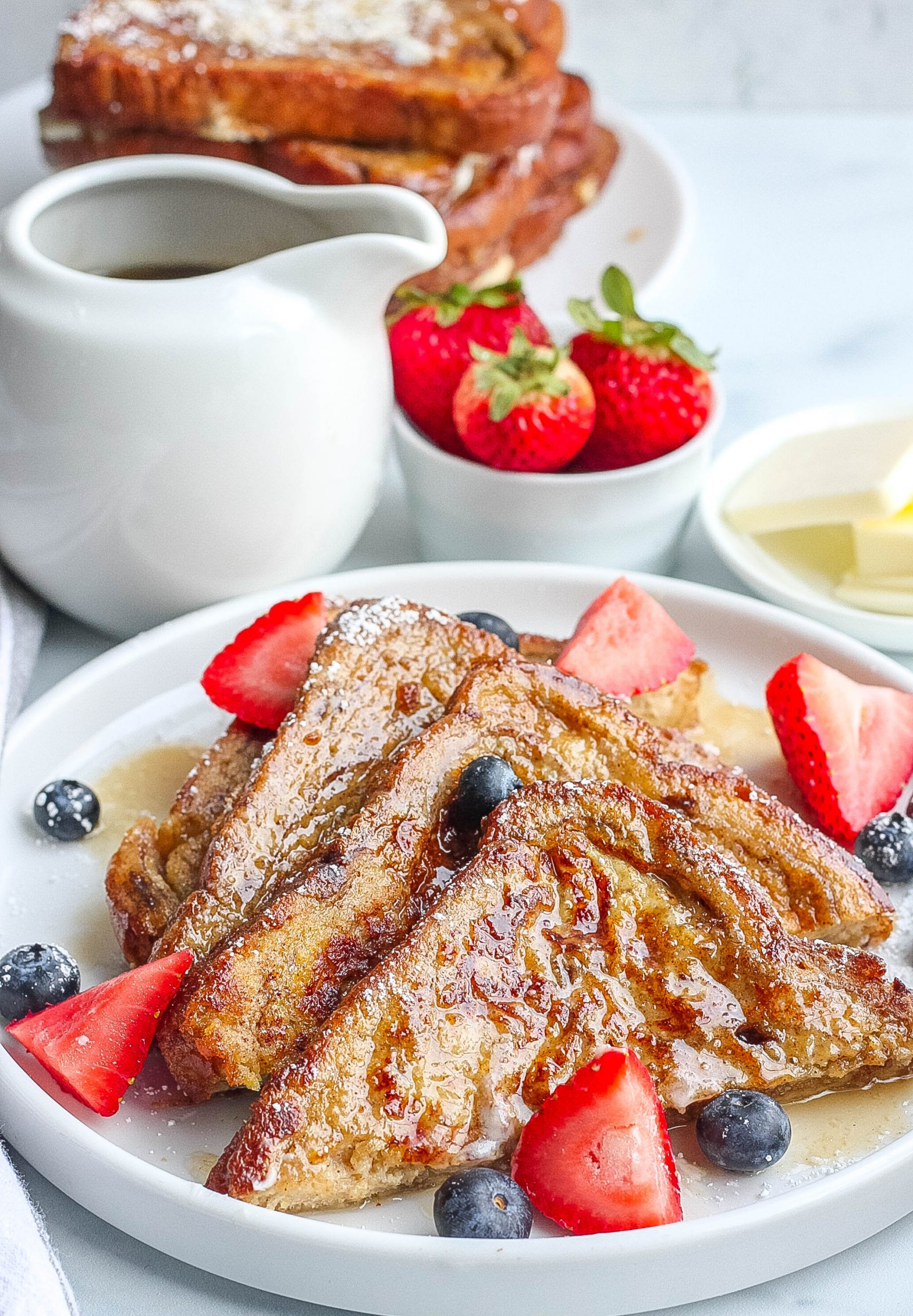 plate of french toast with syrup and berries