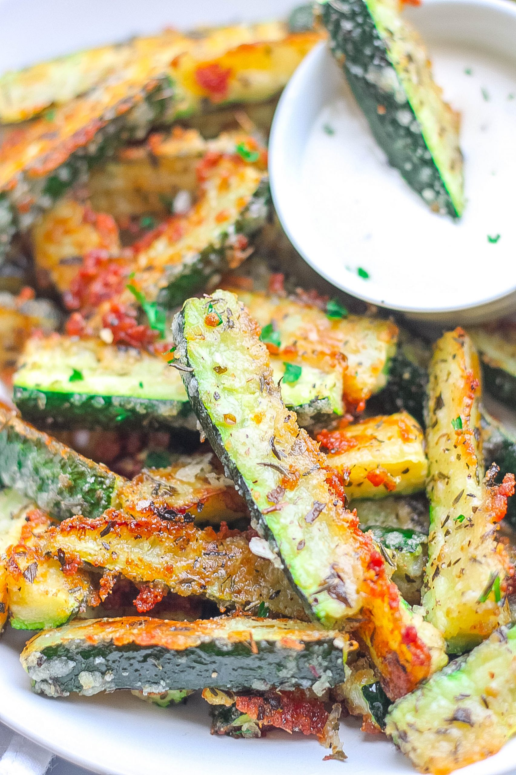 crispy zucchini fries on a plate with dipping sauce