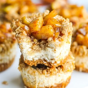 Two mini apple pie cheesecake bites stacked on top of each other. Top bite has a small bite taken out of it.