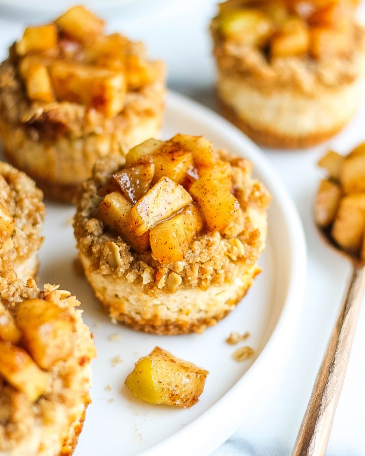 Close-up of mini apple cheesecake bites on a circular white plater.
