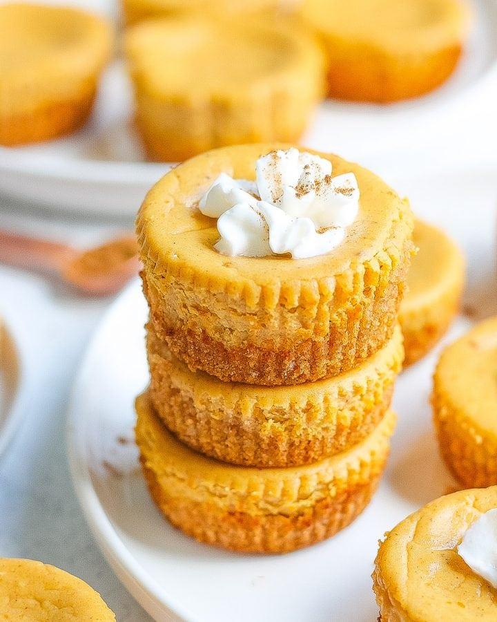 three mini pumpkin pie cheesecakes on white plate with whipped cream