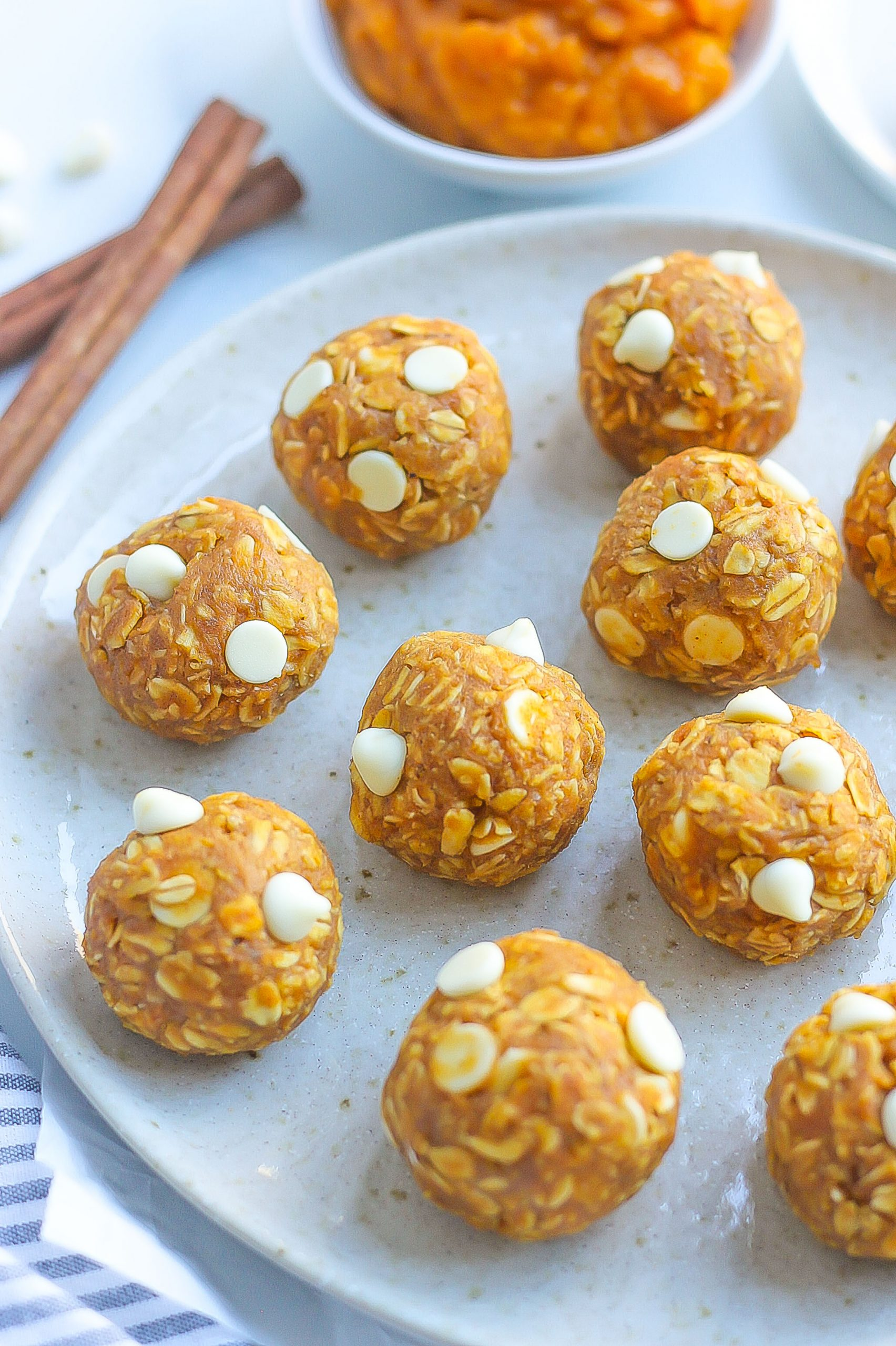 pumpkin energy bites with white chocolate chips on white plate
