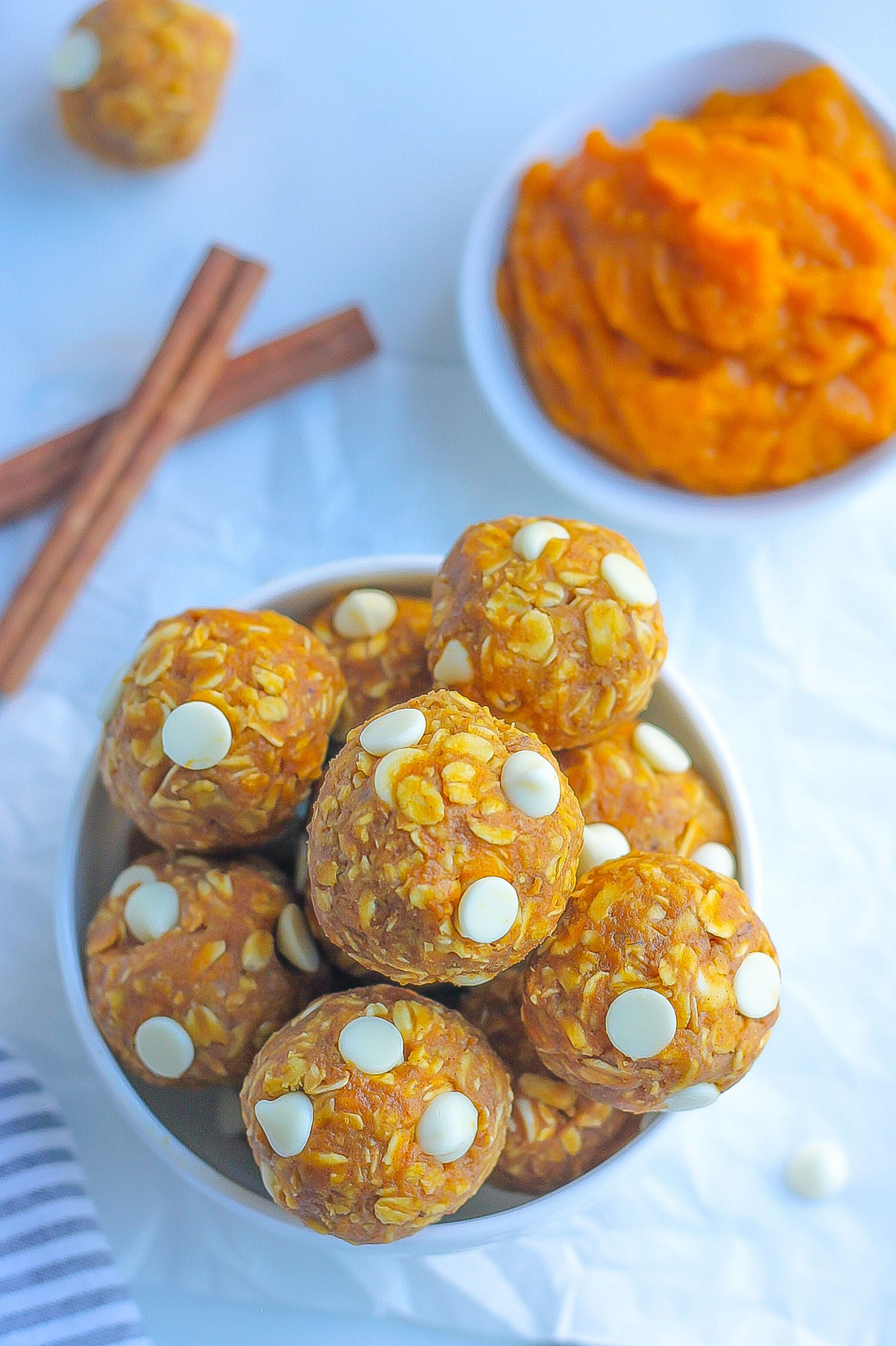 close image of bowl of pumpkin energy bites with white chocolate chips and cinnamon sticks